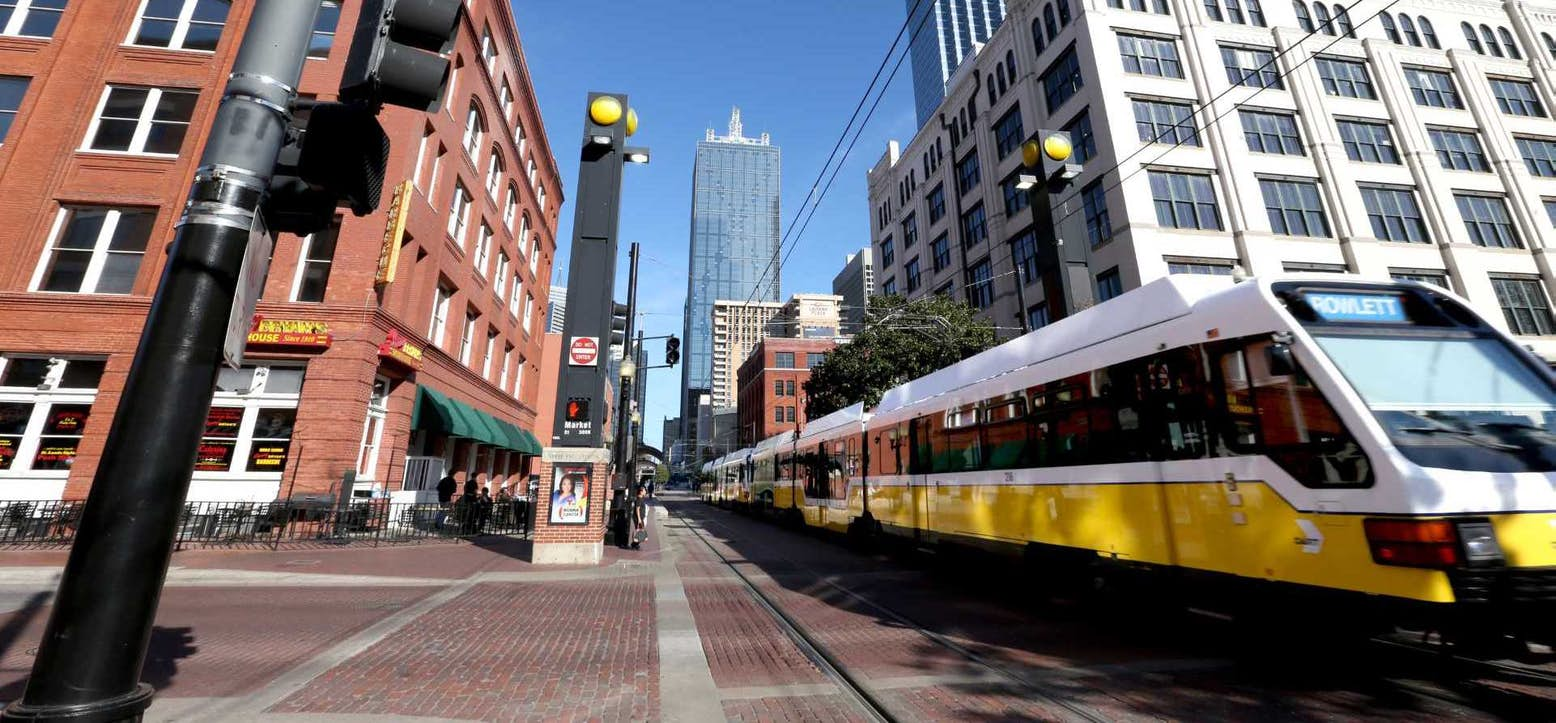 A busy street in Dallas with a trolley train as the focus